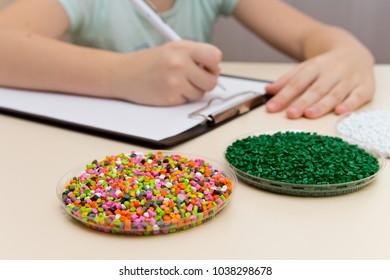 Laboratory assistant inspections plastic pellets for industry. Plastic raw materials in granules . Polymer, plastic resin. The dye in the granules of polypropylene and polyethylene.