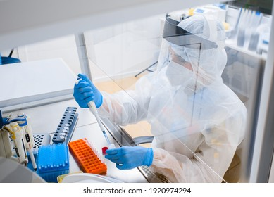 Laboratory assistant in a protective suit and mask in a modern prc laboratory
