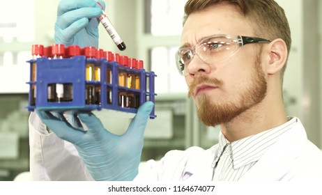The laboratory assistant special glasses for eye protection. He lifted the stand with test tubes to the level of the face. The guy carefully takes out each test with the assays