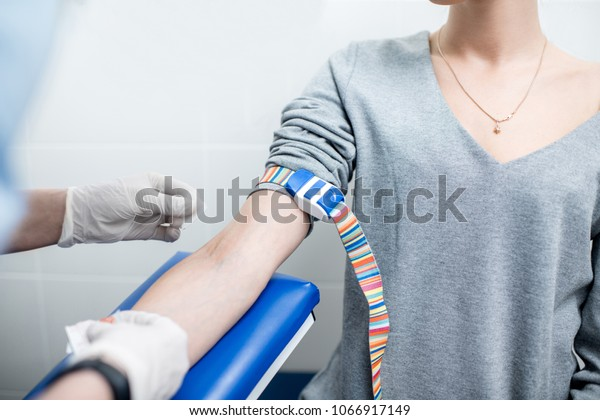 Laboratory assistant taking blood with vacuum capsule for test from the arm vein in the laboratory