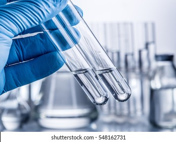 Laboratory beakers in analyst's hand in plastic glove.