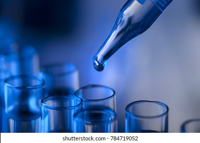 Laboratory beakers, microscope, pipette. Science experiment concept background.