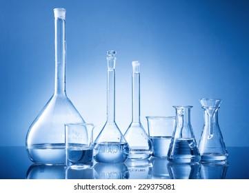 Laboratory equipment, bottles, flasks on blue background