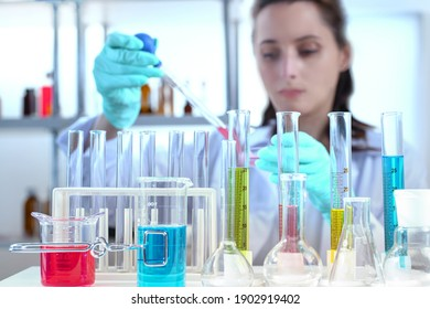 laboratory equipment, supplies, jars, bottles, cylinders, beakers. Lab assistant holding petri dish, pipetting liquid in defocus