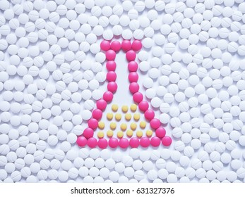 Laboratory flask contained solution made by pink and yellows pills on white tablets background. Creative idea for new drugs, pharmaceutical analysis, research development and chemical concept.