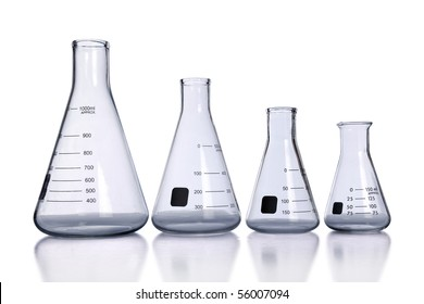 Laboratory flasks of different sizes with reflection on table