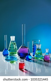 Laboratory Glass With Colorful Liquid. Close Up Of Laboratory Transparent Glassware With Multicolor Fluid On Table In Chemical Lab. Laboratory Equipment. Chemical Research. High Quality Image.