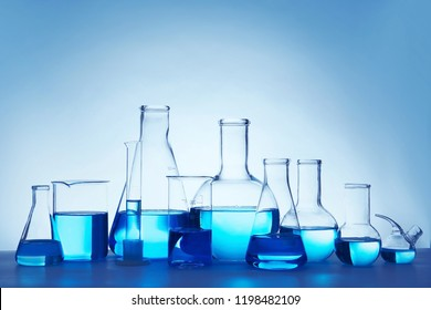 Laboratory glassware for chemical analysis with blue liquid on table against white background