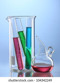 Laboratory glassware with color liquid and with reflection on blue background