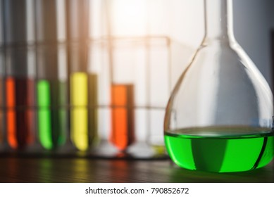 Laboratory glassware containing colorful chemical liquid, lab research and development concept