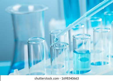 Laboratory glassware with a dropper dripping liquid into a test tube. scientific laboratory test tubes, laboratory equipment