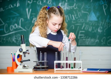 Laboratory glassware. Future microbiologist. School laboratory. Girl smart student conduct school experiment. School pupil study chemical liquids. School chemistry lesson. Test tubes with substances.