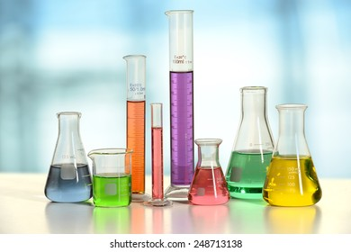 Laboratory glassware with liquids of different colors on white table - With clipping path on glass