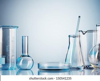 Laboratory glassware on color background
