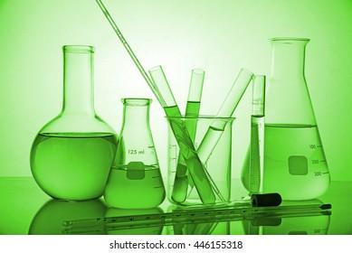 Laboratory glassware on green background