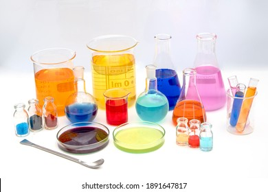 Laboratory glassware with various colored liquids in chemistry laboratory. Volumetric laboratory glassware over white background
