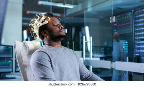 In Laboratory Man Wearing Brainwave Scanning Headset Sits in a Chair with Closed Eyes. Monitors Show EEG Reading and Graphical Brain Model. In the Modern Brain Study/ Neurological Research Laboratory.