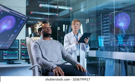 In Laboratory Man Wearing Brainwave Scanning Headset Sits in a Chair while Scientist with Tablet Computer Supervises Process. Monitors Show EEG Reading and Graphical Brain Model.