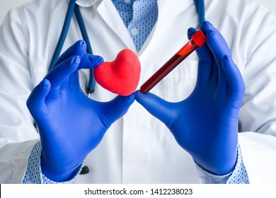 Laboratory medical diagnostics, tests for heart and cardiovascular concept photo. Doctor or laboratory technician holds in one hand laboratory test tube with blood, in other hand - figure of heart