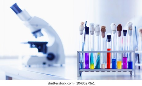 Laboratory metal microscope and test tubes with liquid on blue background