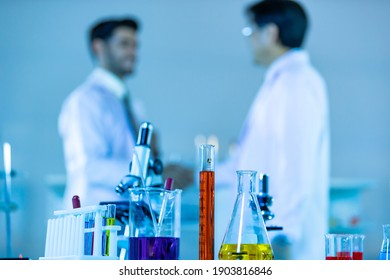 Laboratory Research - Scientific glassware with blur scientist researching background.
