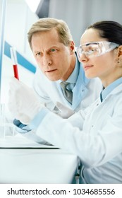 Laboratory Research. Scientists Doing Blood Analysis. Portrait Of Young Female And Male Doctors In Lab Coats Holding Test Tube With Blood Sample, Doing Medical Test. Clinical Laboratory. High Quality