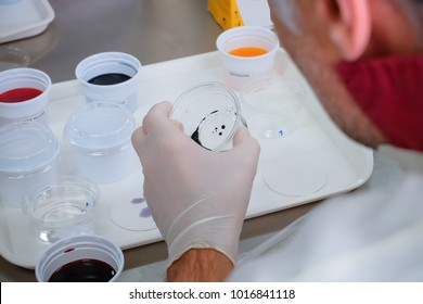 In laboratory, Scientist hold dropper with examine sample of various color of solution