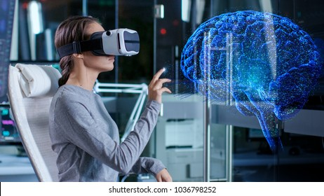 In Laboratory Scientist Wearing Virtual Reality Headset Sitting in a Chair Interacts With Brain Projection Hologram, Showing Neurological Data. Modern Brain Study/ Neurological Research Center.