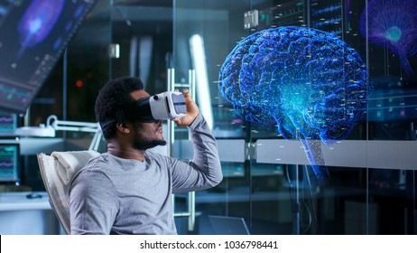 In Laboratory Scientist Wearing Virtual Reality Headset Sitting in a Chair Interacts With Monitors Showing Brain Activity, and Neurological Data. Brain hologram.