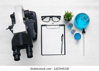Laboratory table with a blank paper sheet of researching results, microscope and a chemical reagent liquids background with copy space. Medical examination mock up.