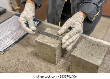 Laboratory for testing building materials. Lab technician measures the size of a concrete cube using a metal ruler.