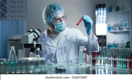 Laboratory worker studying blood samples to detect pathologies, medical research
