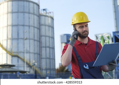 laborer outside a factory working dressed with safety overalls equipment
