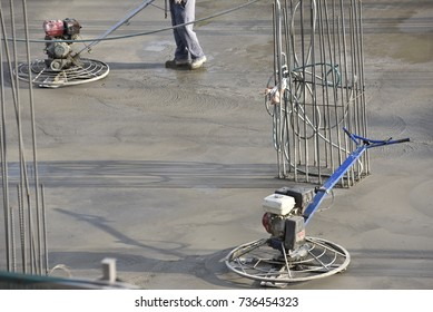 """Laborer polishing sand and cement screed floor with """"Walk-behind"""" power trowel """"helicopters"""", and second one is off"""