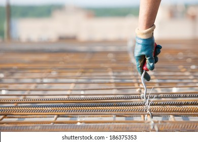 Laborer worker installing binding wires to reinforcement steel bars at construction site during concrete pouring works with formwork. Close up