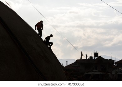 Laborers descend the Boudhanath Stupa during post earthquake repairs in Kathmandu, Nepal.