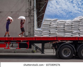 Laborers are loading bags of sugar on truck at industrial factory.