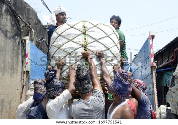 Labors unload truck of vegetables at a wholesale market during the nation wide lock down imposed on the wake of COVID 19 Coronavirus on April 1,2020 in Calcutta, India.