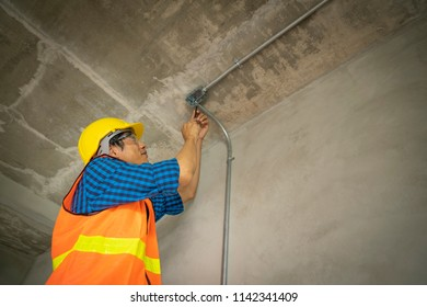 Labour and worker with goggle and helmet during used electric drilling for tight screw.Architech concept.