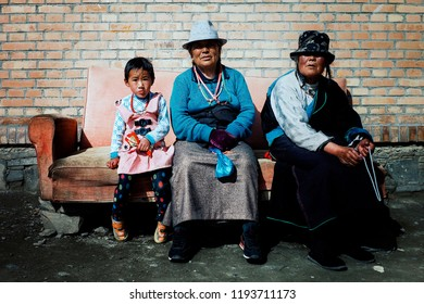 Labrang Monastery, Xiahe, Gansu Province / China - JUN 6 2011: tibetan buddhist pilgrim woman and a young girl waiting outside a temple on a couch