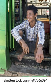 LABUAN BAJO, FLORES, INDONESIA 22 JUN 2017: A smiling young man sit on vehicle side door selling gallons of petrol by containers.