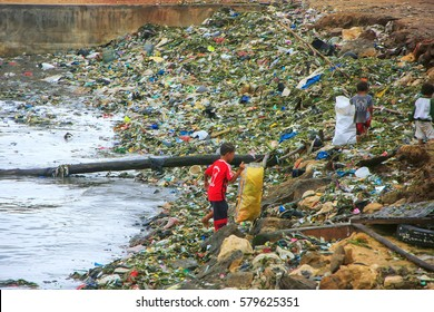 LABUAN BAJO, INDONESIA-MARCH 17: Unidentified boys go through garbage at sea coast on March 17,2012 in Labuan Bajo, Flores, Indonesia. The local economy is centered around the ferry port and tourism.