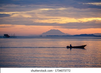 Labuan F.T, Malaysia- May 17, 2020: Silhouette of fisherman with Mount Kinabalu as a background during sunrise view from Kg. Tanjung Aru Labuan F.T Malaysia.