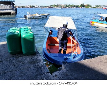 Labuan, Malaysia. December 6, 2018. A passenger jump over a boat to embark at Labuan Ferry Terminal to board a vessel at anchorage