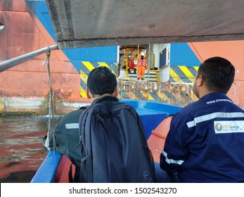 Labuan, Malaysia - December 6, 2018. Offshore workers embarking a vessel via swing rope and pilot ladders from a water taxi at Labuan outer port limit anchorage