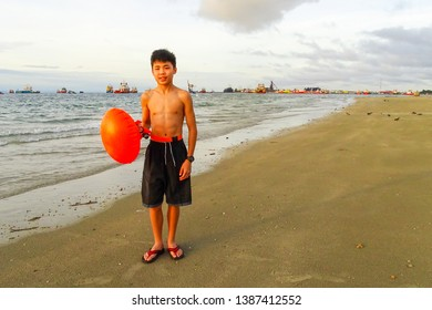 Labuan,Malaysia-Apr 27,2019:Boy in a striped swimming shorts with his orange safety flotation in the beach of Labuan island,Malaysia.