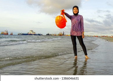 Labuan,Malaysia-Apr 27,2019:Happy muslim woman wearing hijab swimming suits with her orange safety flotation in the beach of Labuan island,Malaysia.