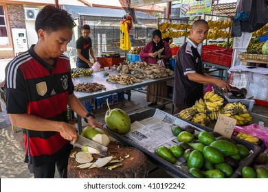Labuan,Malaysia-April 24,2016: A vendor prepares fresh green drinking coconuts in the local market at Labuan,Malaysia.