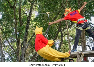 Labuan,Malaysia-Feb 12,2017:Happy girl in teddy bear costume enjoying on a flying fox in Labuan,Malaysia.There will be more ziplines in Malaysia,especially when there have so much natural rainforest.