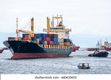 Labuan,Malaysia-July 15,2016:A tugboat maneuvers vessel by pushing or towing the container ship with full of cargo in Labuan,Malaysia.The abolishment of cabotage policy is set to benefit the island
